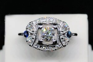 vintage inspired wide engagement ring with blue sapphires and center diamond