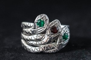 three snake intertwined to make a ring with emeralds and garnet in the head