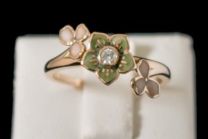 green enamel flower with center diamond and blush enamel petals