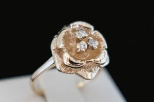 rose shaped yellow gold ring with three small diamonds in the center