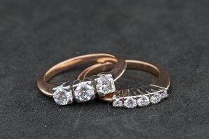 guyana gold diamond engagement ring sitting on top of guyana gold and diamond wedding ring