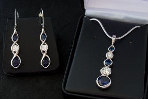 diamond and sapphire dangle earrings sitting next to a diamond and sapphire pendant with snake chain in jewelry box