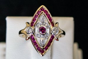yellow gold ring with a marquise shape of rubies with diamond accents