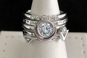 five white gold and diamond rings stacked together