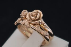 custom rose gold engagement ring with large rose in center and smaller rose on the side with a leaf wedding ring