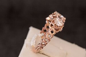 10k rose gold and moissanite flower engagement ring with twisted sides