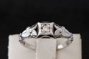 top view of vintage white gold and diamond engagement ring with flower shaped design on the band